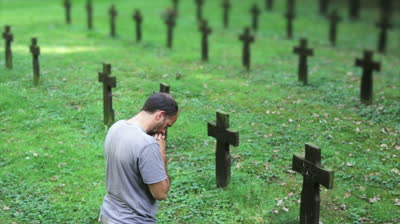 stock-footage-man-praying-over-a-cross-and-grave-at-the-memorial-cemetery